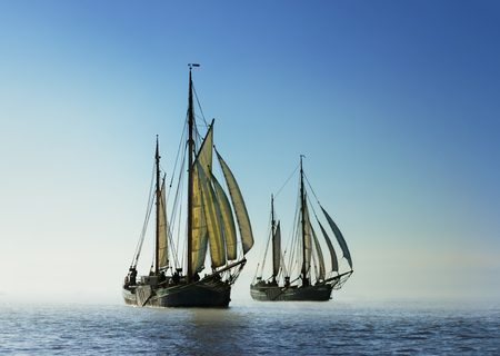 shores: Backlight image of two traditional sailing boats under sail, sailing on the ocean. Adventure concept. Reaching for new shores.