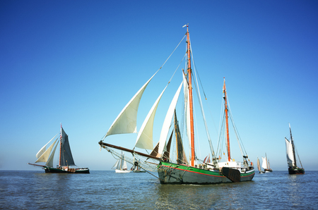 Blue color image of a fleet of traditional sailing ships on the ocean. Stock Photo