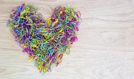 corazon humano: banda de goma de colores en forma de coraz�n en el fondo de madera
