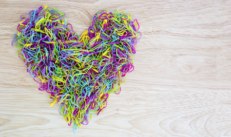plastic heart: Colorful rubber band in heart shape on wood background Stock Photo