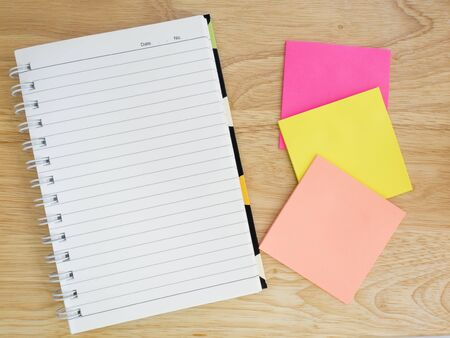 note paper: Blank notebook and colorful note paper on wood background