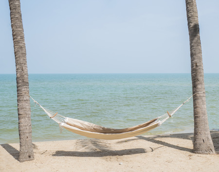 Hammock on the beach under the blue sky in the afternoon