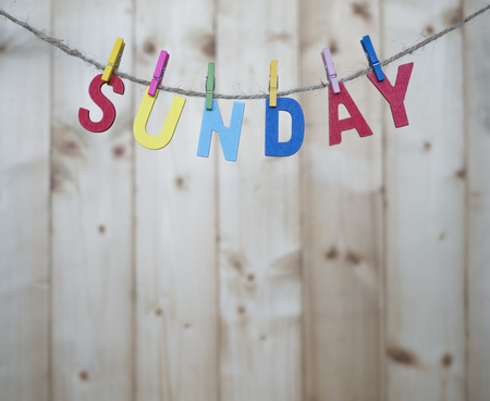 weekdays: Sunday word by wooden letters hang with rope on wood background (Weekdays word series) Stock Photo
