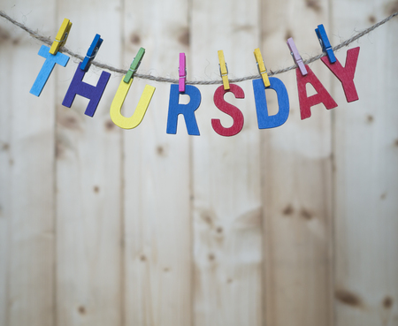 green yellow: Thursday word by wooden letters hang with rope on wood background (Weekdays word series)