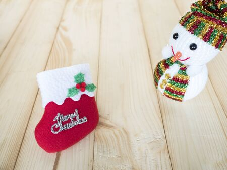 snowman wood: Snowman and christmas sock decoration for Christmas Holiday on wood background