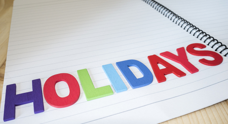and spelling: Word spelling Holidays on notebook page with wood background (Business concept)