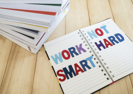and spelling: Word spelling Work Smart Not Hard on notebook page with wood background (Business concept) Stock Photo