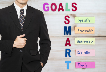 setting goals: One business man  wear black suit stand on SMART Goal in wood background (Business Concept) Stock Photo