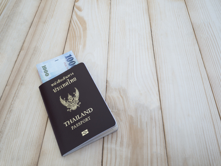 customs official: Thailand passport and Taiwan banknote on wood background Stock Photo