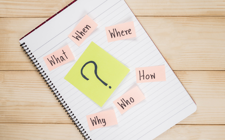 why: Questions what, when, where, why, who, how on white notebook with wood background