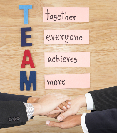 join the team: Business partners making pile of hands for TEAM (Business Concept)