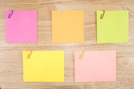 Colorful sticky note and paper clip on wood background