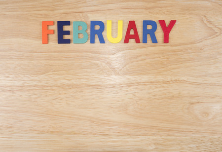 Word spelling month in the year February by wooden letters on wood background (Month name word series)