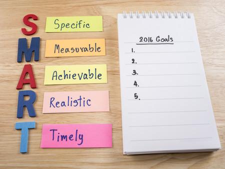 metas: Objetivos SMART y 2016 Goles en el cuaderno en el fondo de madera (Concepto de negocio)