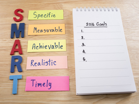 goal: SMART Goals and 2016 Goals in notebook on wood background (Business Concept) Stock Photo