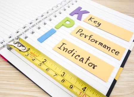 kpi: KPI (Key Performance Indicator) on white notebook with wood background (Business concept) Stock Photo