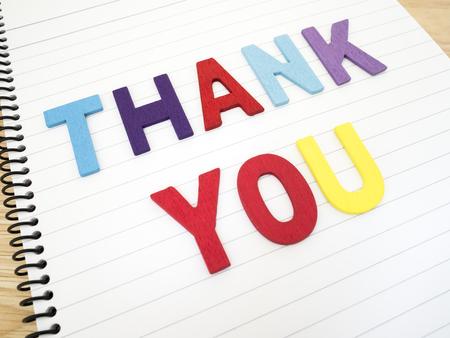"""agradecimiento: Ortografía palabra """"Gracias"""" en el cuaderno blanco con fondo de madera"""
