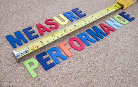 「パフォーマンスの測定」のスペルとコルク ボード背景上のテープを測定の単語 写真素材