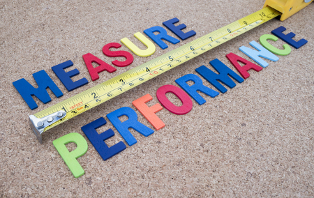 measurement tape: Word spelling Measure Performance and measuring tape on cork board background Stock Photo