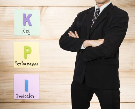 kpi: One business man  wear black suit stand on KPI background (Business concept)