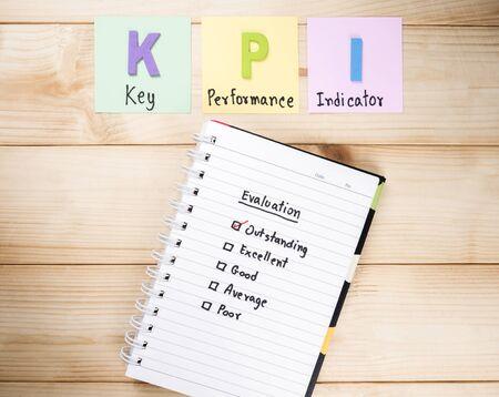 performance improvement: KPI (Key Performance Indicator) and Performance Evaluation check box on notebook with wood background Stock Photo