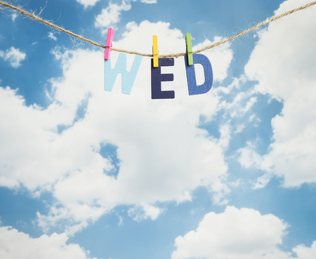 wed: Wed word by wooden letters hang with rope on blue sky background (Weekdays word series)