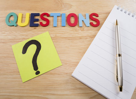mark pen: Word spelling Questions, question mark, pen and white notebook on wood background Stock Photo