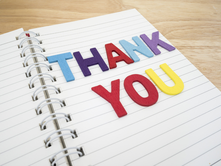 Word spelling Thank you on white notebook with wood background