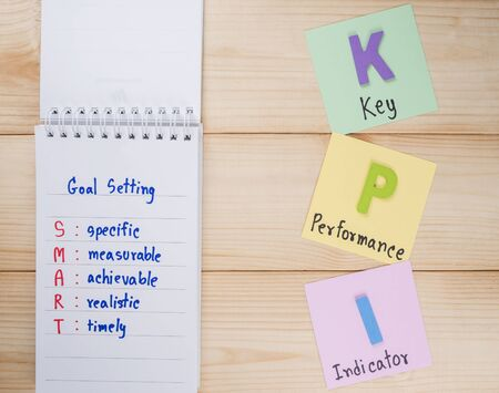 KPI (Key Performance Indicator) and SMART Goal on notebook with wood background Stock Photo