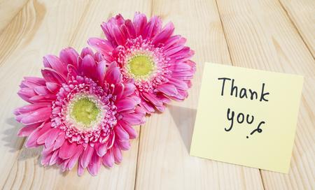 """agradecimiento: flores de color rosa y la palabra """"Gracias"""" en el papel nota de color con fondo de madera"""
