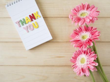 """gratefulness: flores de color rosa y la palabra """"Gracias"""" en el papel nota de color con fondo de madera"""