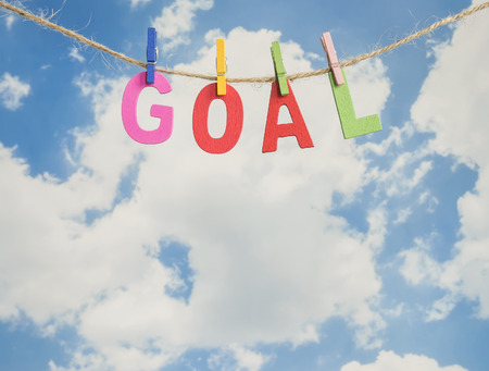 achievement concept: Word Goal by wooden letters hang with rope on blue sky background (Business Concept)
