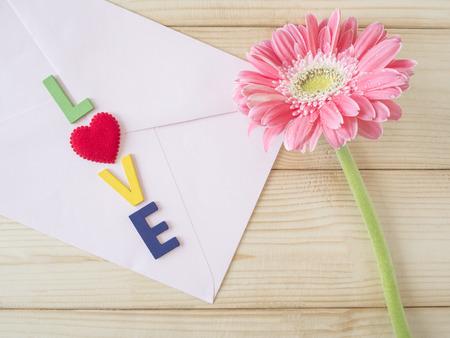 "Pink flower and word ""Love"" on pink envelope in love concept on wood background, Valentines day Reklamní fotografie"