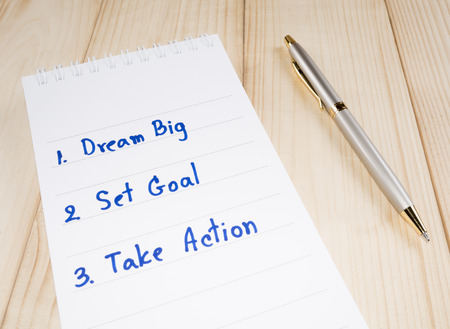 set goal: Dream Big, Set Goal , Take Action, handwriting on notebook with pen on wood background