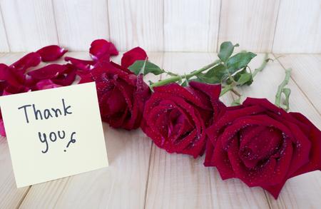 """agradecimiento: Rosa roja y la palabra """"Gracias"""" en el papel nota de color con fondo de madera Foto de archivo"""