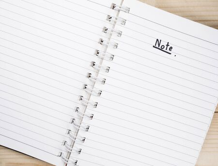 take a note: White blank notebook put on wood background for take a note