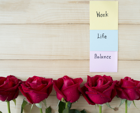 achievement concept: Word Work Life Balance on colorful note paper and pink flowers with wood background Stock Photo