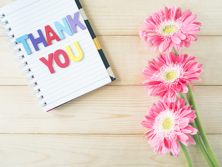 thankfulness: Pink flower and word Thank you on white notebook with wood background
