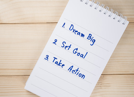 set goal: Dream Big, Set Goal , Take Action, handwriting on notebook with wood background