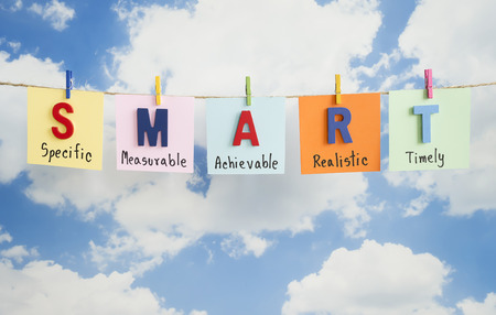 attainable: SMART Goals hang with rope on blue sky background (Business Concept)