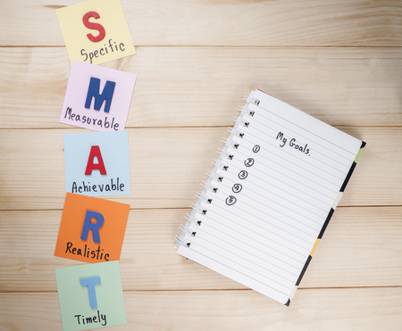 attainable: SMART Goals and My Goals in notebook on wood background (Business Concept)