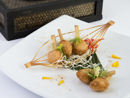 vietnamese food: Fried shrimp with sugar cane (Vietnamese food) on white dish with isolated background Stock Photo