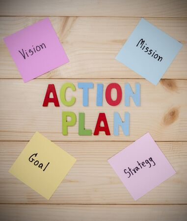 plan de accion: Word Vision Mission Goal Strategy Action Plan on colorful note paper with wood background (Business concept)