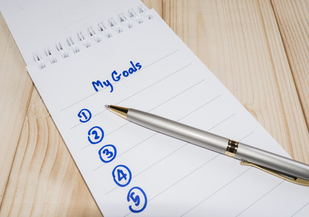 specific: My Goals in notebook on wood background (Business Concept)