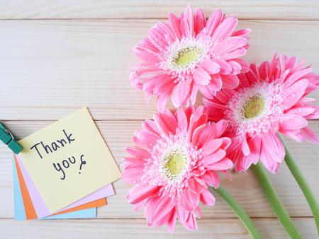 """Roze bloem en het woord """"Thank you"""" op kleurrijke notitie papier met houten achtergrond"""