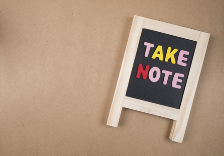 take a note: Word spelling Take Note on black broad with brown paper background (Business concept) Stock Photo