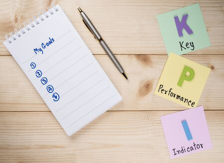 achievable: KPI (Key Performance Indicator) and My Goal on notebook with wood background