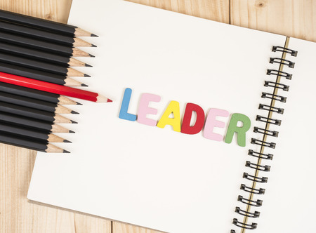 standout: Red pencil standout from black pencil on blank notebook, leadership business concept