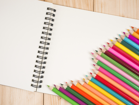 color pencil: Stack of color pencil and blank notebook on wood background (Business Concept) Stock Photo