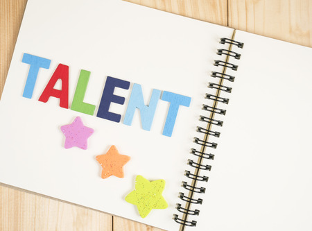knack: Word spell Talent and star on blank notebook with wood background (Business Concept)